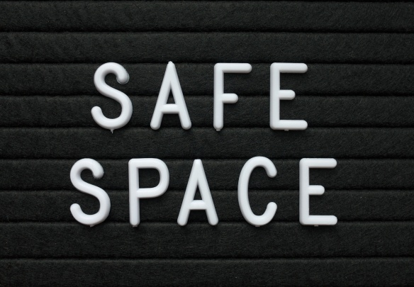 The words Safe Space in white plastic letters on a black letter board to indicate a place or environment where people can feel protected